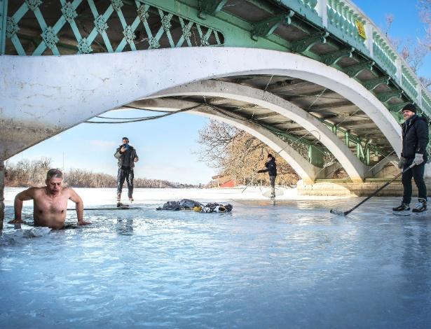 Morador de uma das ilhas de Toronto mergulha nas águas congeladas de rio após patinar no gelo