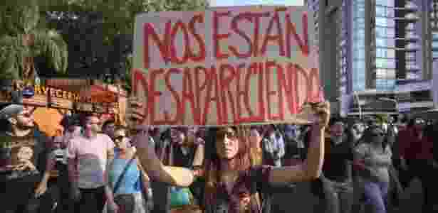 Manifestante segura cartaz dizendo 'Estão desaparecendo com a gente' em protesto contra o desaparecimento dos universitários - EPA - EPA