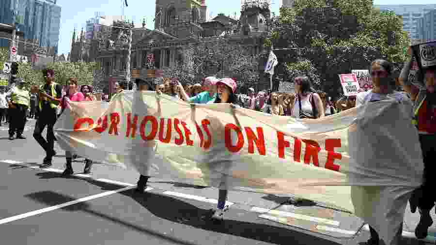 """29.11.2019 - Estudantes fazem protesto por ação governamental contra o aquecimento global, na Austrália. Na faixa, a mensagem: """"nossa casa está pegando fogo"""" - Getty Images"""