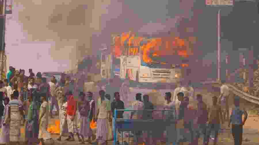 14.dez.2019 - Manifestantes colocam fogo em ônibus durante protesto contra nova lei de cidadania - STR/AFP