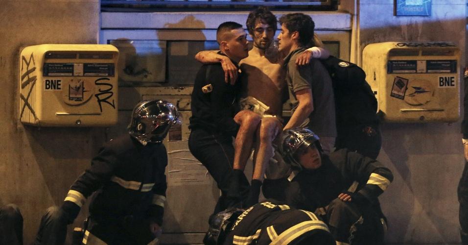 13.nov.2015 - Bombeiros carregam um homem ferido próximo à sala de concertos Bataclan, em Paris, na França, onde um homem armado fez reféns. Agências de notícias falam em 100 pessoas dentro do local. Tiroteios e explosões aconteceram na noite desta sexta-feira (13) na capital francesa. A polícia relatou ao menos duas explosões nas proximidades do estádio Stade de France, onde o presidente francês, François Hollande, acompanhava um amistoso da seleção francesa