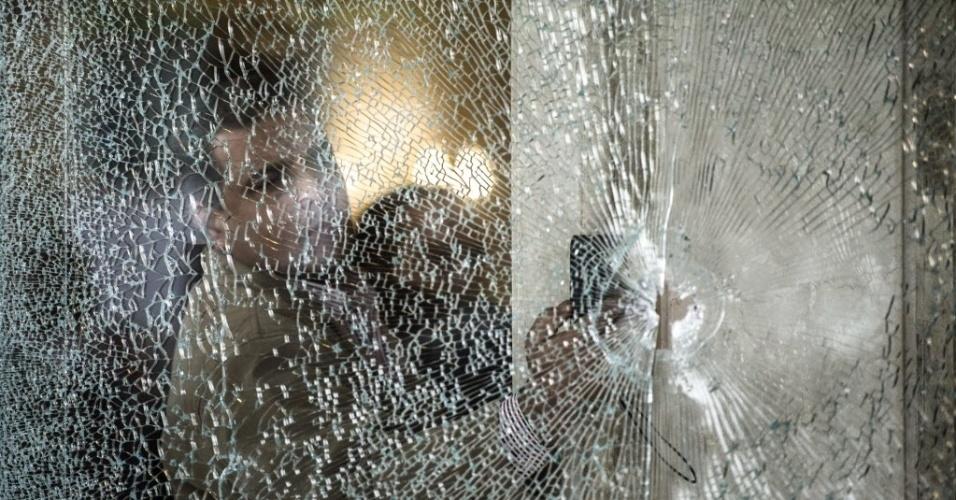 7.jan.2016 - Um especialista forense inspeciona janela cravejada de bala na entrada do hotel Três Pirâmides, no distrito de al-Haram. no Cairo (Egito), depois que homens armados dispararam contra policiais próximo à área externa do hotel. Ninguém foi ferido