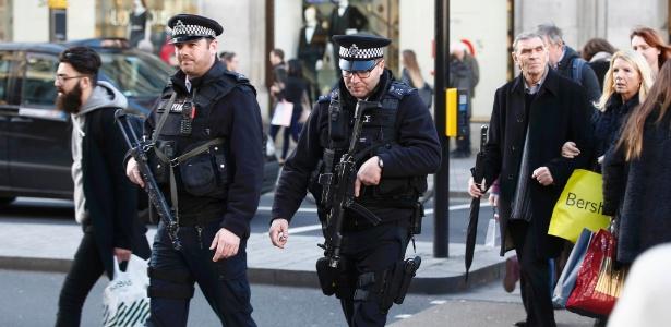 Policiais armados andam em meio a pedestres na Oxford Street, em Londres