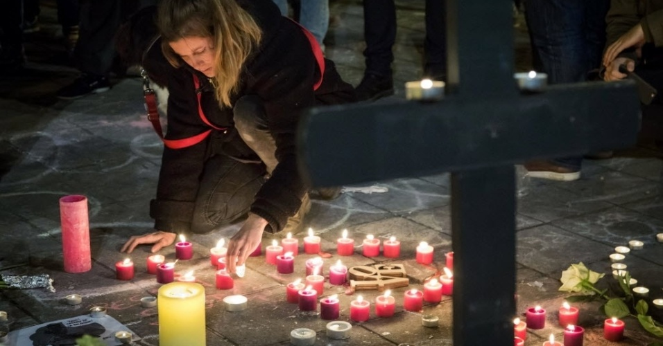 22.mar.2016 - Mulher monta um coração com velas vermelhas durante série de homenagens às vítimas dos três ataques à bomba que o grupo jihadista Estado Islâmico executou em Bruxelas, na Bélgica