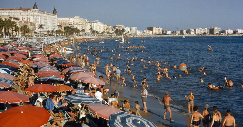 27.mai.2016 - Alguns banhistas se protegem do sol enquanto outros se bronzeiam numa praia em Cannes, no sul da França