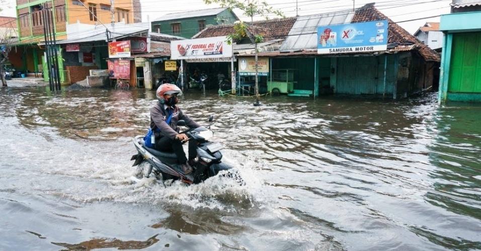 """8.jun.2016 - Homem atravessa rua alagada em Semarang, Indonésia. O fenômeno climático """"La Niña"""", que resfria as temperaturas médias das águas do oceano Pacífico, aumentam a umidade do sudeste asiático"""