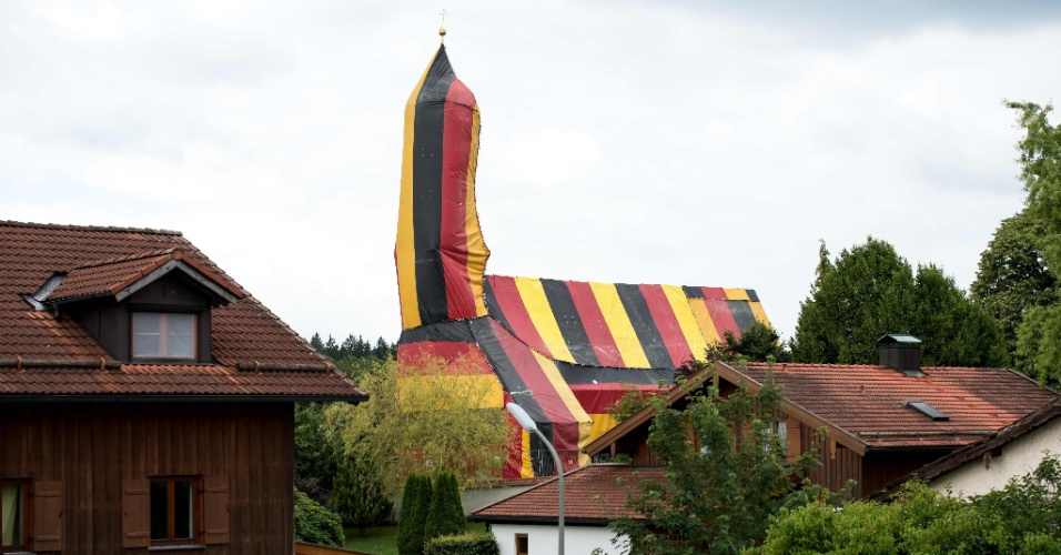 6.jul.2016 - Uma capa gigante com as cores da bandeira alemã cobre a igreja de Sankt Coloman, em Kirchseeon, perto de Munique, no sul da Alemanha. O motivo do isolamento é um tratamento contra infestação de cupins