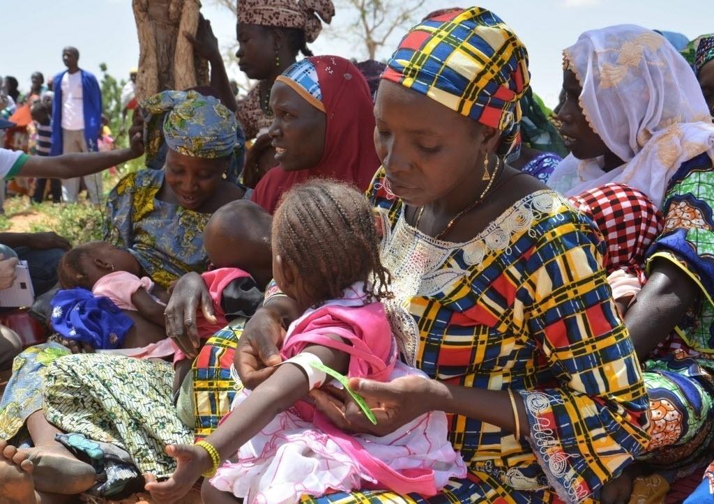 19.jul.2016 - Mãe mede o perímetro braquial (a circunferência superior do braço) da filha com fita métrica para aprender a acompanhar o estado nutricional da criança em uma aula sobre desnutrição no Níger, na África. O país é um dos mais pobres do mundo e sofre com uma taxa de desnutrição de 15%, de acordo com a Organização Mundial da Saúde. O evento aconteceu na última quinta-feira (14) e as imagens foram divulgadas nesta terça-feira