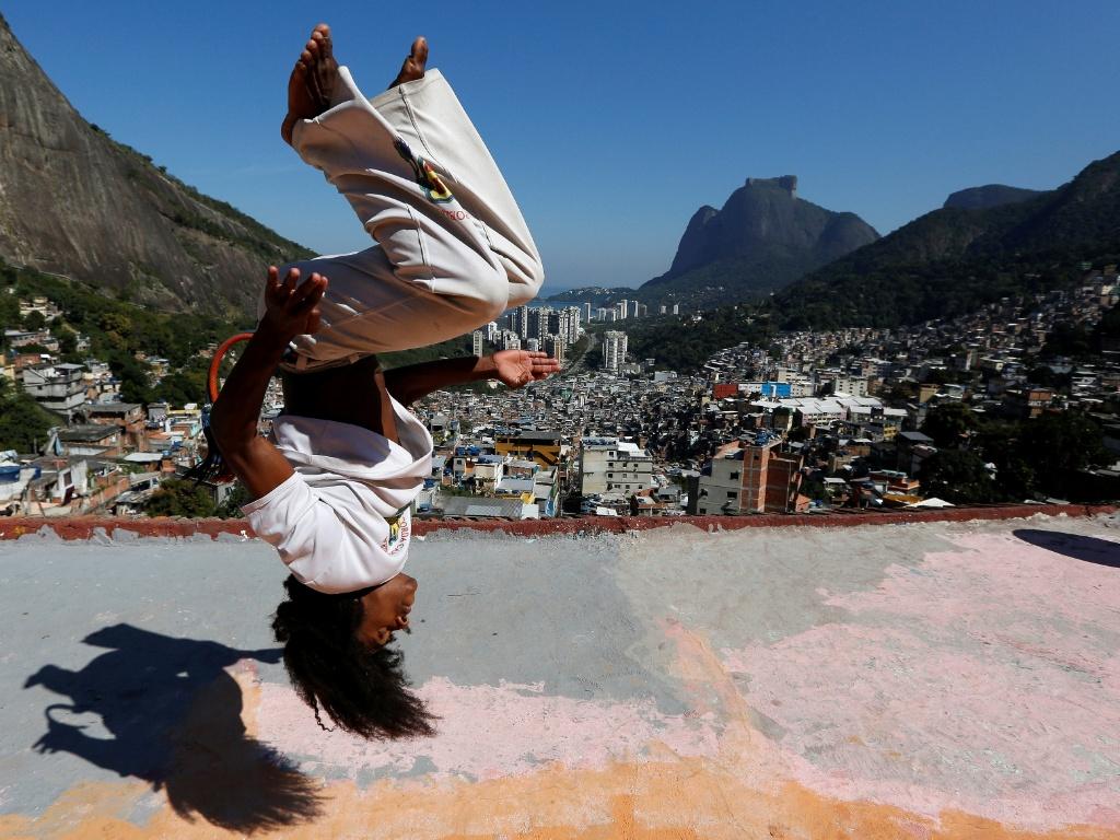 29.jul.2016 - Membro do Acorda-Capoeira faz manobra no telhado de uma casa na favela da Rocinha, no Rio de Janeiro. O grupo desenvolve trabalhos socioculturais e entretém jovens da comunidade com aulas de capoeira, reforço escolar, línguas estrangeiras, teatro, aulas de percussão e danças