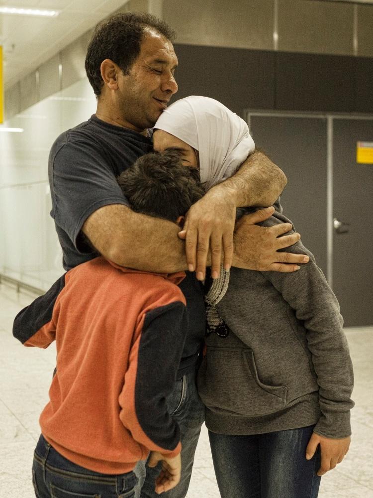 13.mar.2017 - O refugiado sírio Adnan Alkhaled com os filhos Aisar e Sidra na chegada de sua família ao país no aeroporto de Cumbica