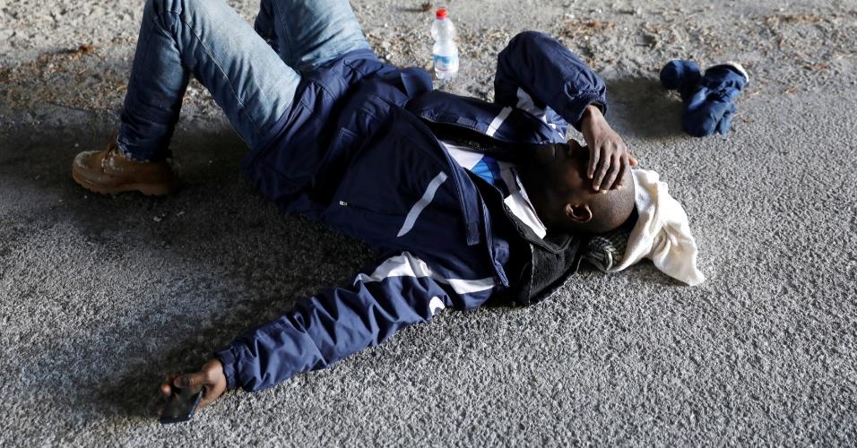 O imigrante da Guiné, Abdullhai, descança após cruzar parte dos Alpes