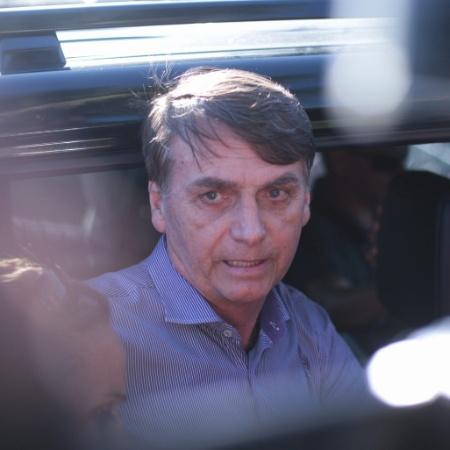 O presidente eleito, Jair Bolsonaro, fala com a imprensa na porta do carro, escoltado por policiais federais - Filipe Cordon/Folhapress