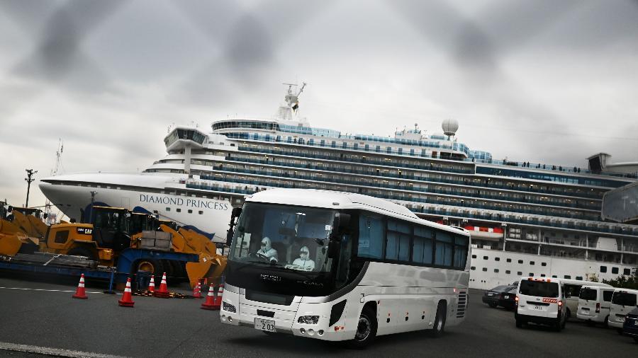 Ônibus transfere passageiros de navio Diamond Princess, em Yokohama, no Japão - CHARLY TRIBALLEAU/AFP