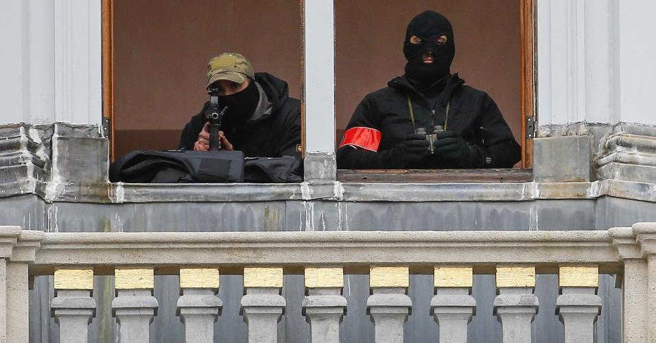 20.nov.2015 - Atiradores da polícia belga, posicionados em um prédio de Bruxelas, observam a movimentação em uma área da Bélgica nesta sexta (20). A segurança foi reforçado na capital belga após os ataques terroristas que mataram 129 pessoas em 13 de novembro na França