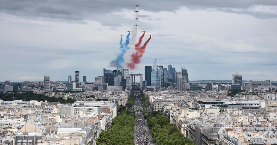 14.jul.2016 - Aviões sobrevoam a avenida Champs Elysees, em Paris, e soltam fumaça com as cores da bandeira francesa durante parada militar pela comemoração da Queda da Bastilha. A festa nacional francesa é um feriado nacional celebrado em memória ao episódio histórico da Tomada da Bastilha, em 1789, quando teve início o caráter popular da Revolução Francesa. Neste ano, tropas da Austrália e Nova Zelândia foram convidadas para o evento, que contará com 3.000 soldados, 85 aeronaves e 200 veículos militares