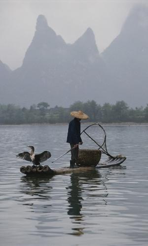 Um pescador no rio Li, em Guangxi, na China. Alguns pescadores do sudeste do país usam cormorões, também conhecido como biguá (pássaros aquáticos), treinados para ajudar na pesca