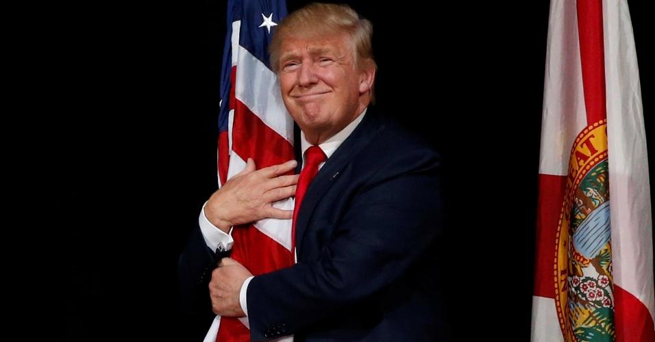 25.out.2016 - O candidato republicano à presidência dos EUA, Donald Trump, abraça a bandeira dos Estados Unidos durante ato de campanha em Tampa, na Flórida