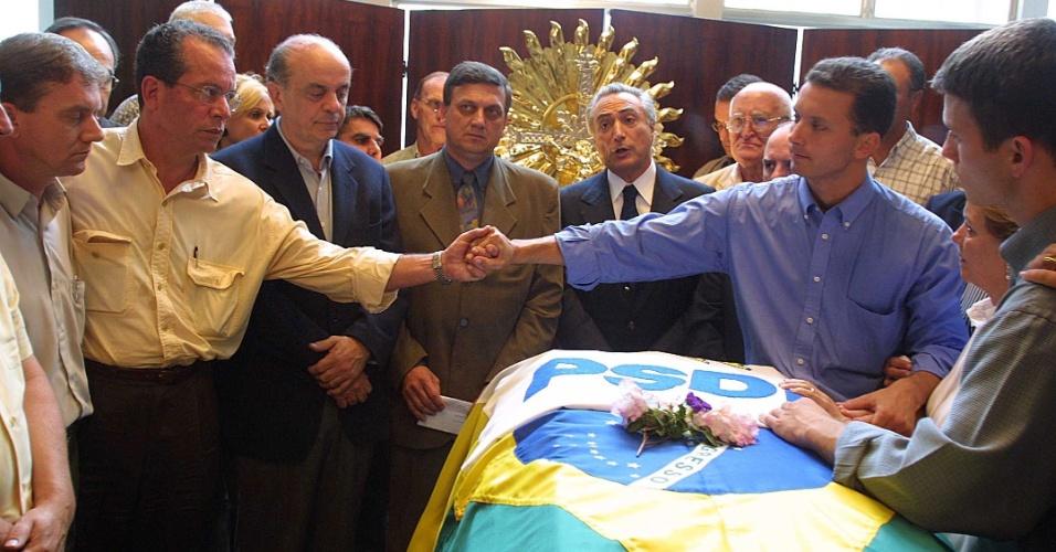 12.fev.2002 - Nelson Marchezan Júnior é cumprimentado por José Aníbal (PSDB-SP), durante o velório do pai, Nelson Marchezan, então deputado federal tucano pelo Rio Grande do Sul. Também marcaram presença Michel Temer (ao fundo na foto) e José Serra (à esquerda)
