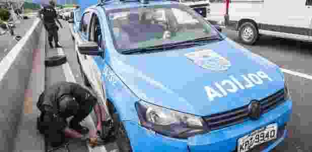 22.fev.2018 - Carro da Policia Militar com pneu rasgado no corredor Presidente Tancredo Neves, próximo ao bairro Magalhães Bastos, na zona norte do Rio  - Danilo Verpa/Folhapress - Danilo Verpa/Folhapress