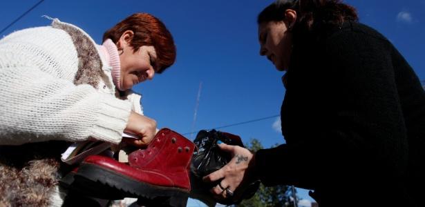 Mulher troca sapato por carteira na periferia de Buenos Aires; com dinheiro desvalorizado, Argentina vê a volta dos clubes de troca - MARTIN ACOSTA / Reuters