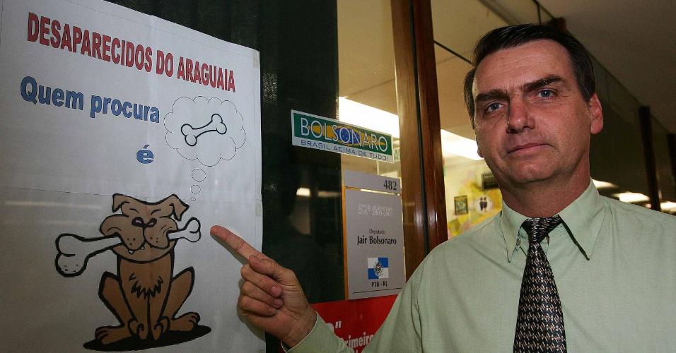 1.dez.2004 - O então deputado Jair Bolsonaro exibe um cartaz onde protesta contra a procura dos restos mortais dos guerrilheiros do Araguaia, em seu gabinete no Congresso Nacional