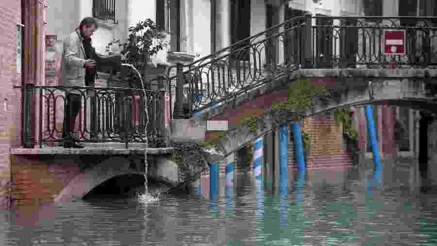 Um homem seca uma bota em uma rua inundada em Veneza, na Itália. O governo da cidade declarou estado de emergência - ilippo Monteforte/AFP