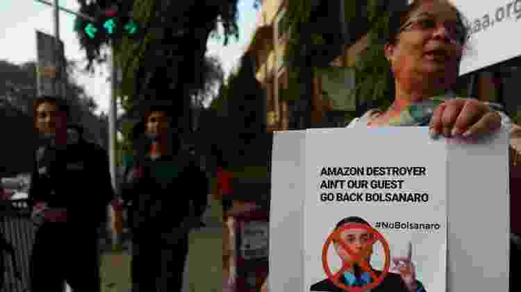 'Destruidor da Amazônia não é nosso convidado. Volte para casa, Bolsonaro', diz cartaz de protesto em inglês durante a visita do presidente brasileiro à Índia, em janeiro de 2020 - Getty Images - Getty Images