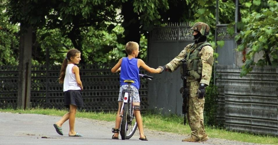 14.jul.2015 - Criança cumprimenta membro da Guarda Nacional da Ucrânia que patrulha as ruas de Borhalom. Três pessoas foram mortas em um novo confronto em 11 de julho entre a polícia e membros do partido radical Pravi Sektor