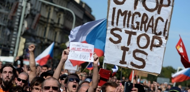 Tchecos seguram cartazes em protesto contra os imigrantes que chegam à Europa