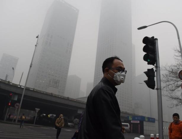 Protegendo-se da poluição, homem usa máscara para caminhar por rua de Pequim