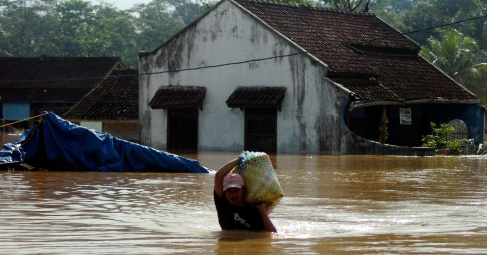 17.mar.2016 - Indonésio carrega seus pertences ao atravessar rua inundada na aldeia de Tanjungsari, na província de Java Oriental. Quatro aldeias no leste da principal ilha indonésia foram inundadas pelo rompimento de uma barragem