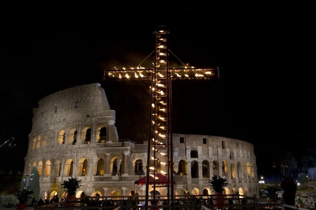 25.mar.2016 - Cruz é instala em frente ao Coliseu, em Roma, para aguardar a chegada do papa Francisco para liderar a Via-Crúcis