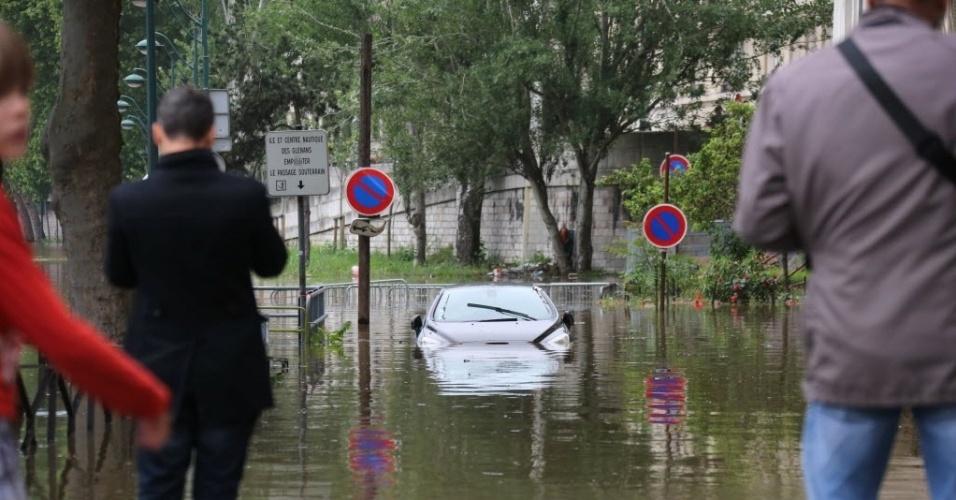 2.jun.2016 - Parisienses param para tirar foto de um carro que ficou submerso com a cheia do rio Sena, em Beaugrenelle. Funcionários do governo colocaram barreiras no local para tentar conter a inundação