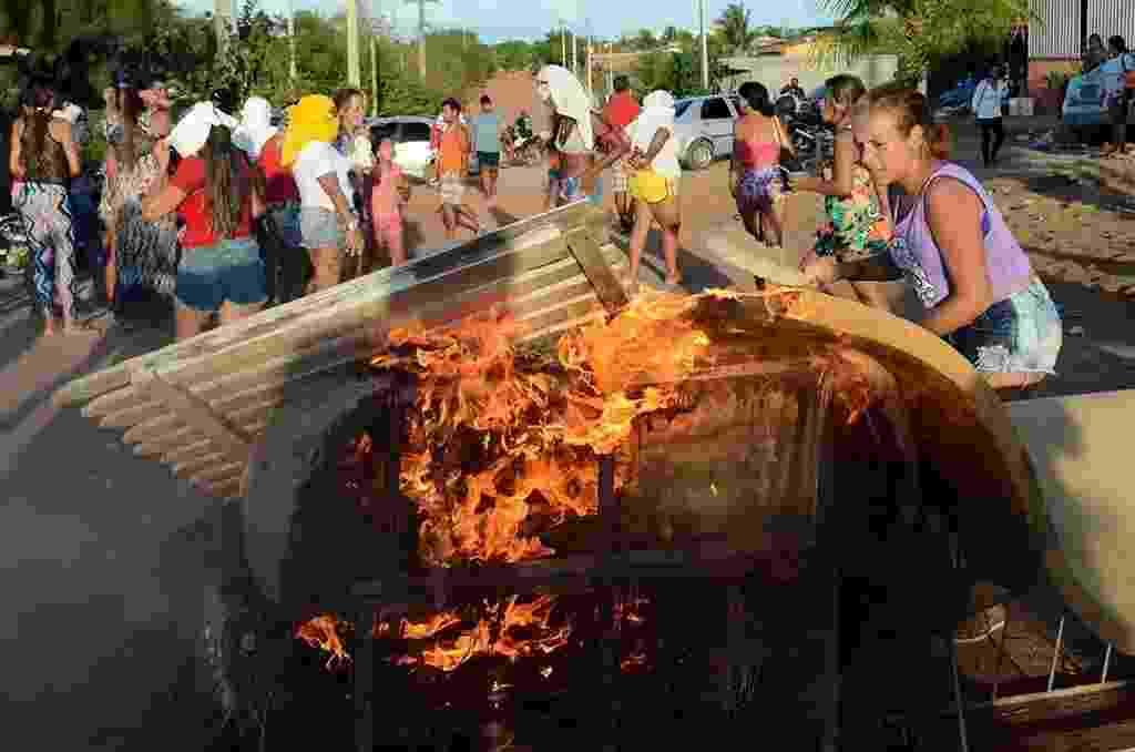 18.jan.2017 - Mulheres protestam contra a transferência de presos da penitenciária de Alcaçuz, em Nísia Floresta (RN). Algumas delas estavam com o rosto coberto. Elas atearam fogo a pedaços de madeira, móveis e pneus para fechar a rua que dá acesso à unidade prisional - Beto Macário/UOL