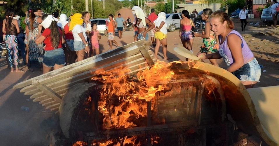 18.jan.2017 - Mulheres protestam contra a transferência de presos da penitenciária de Alcaçuz, em Nísia Floresta (RN). Algumas delas estavam com o rosto coberto. Elas atearam fogo a pedaços de madeira, móveis e pneus para fechar a rua que dá acesso à unidade prisional