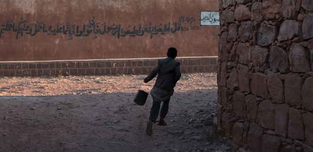 Menino corre nas ruas de Kawkaban, no Iêmen