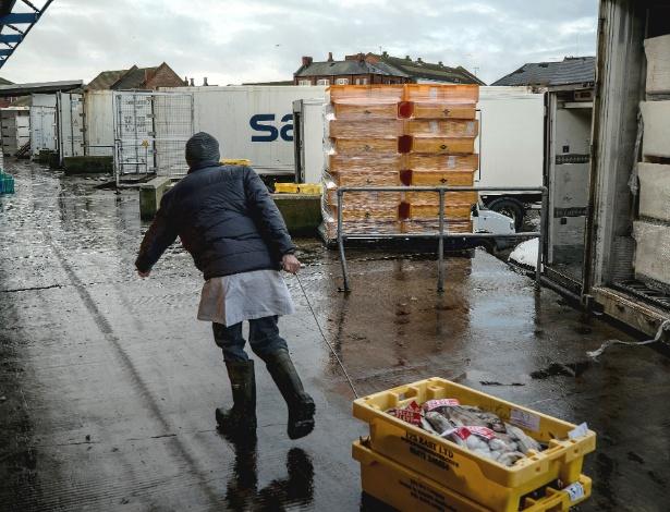Funcionário transporta pescados no Mercado de Peixes de Grimsby, na Inglaterra