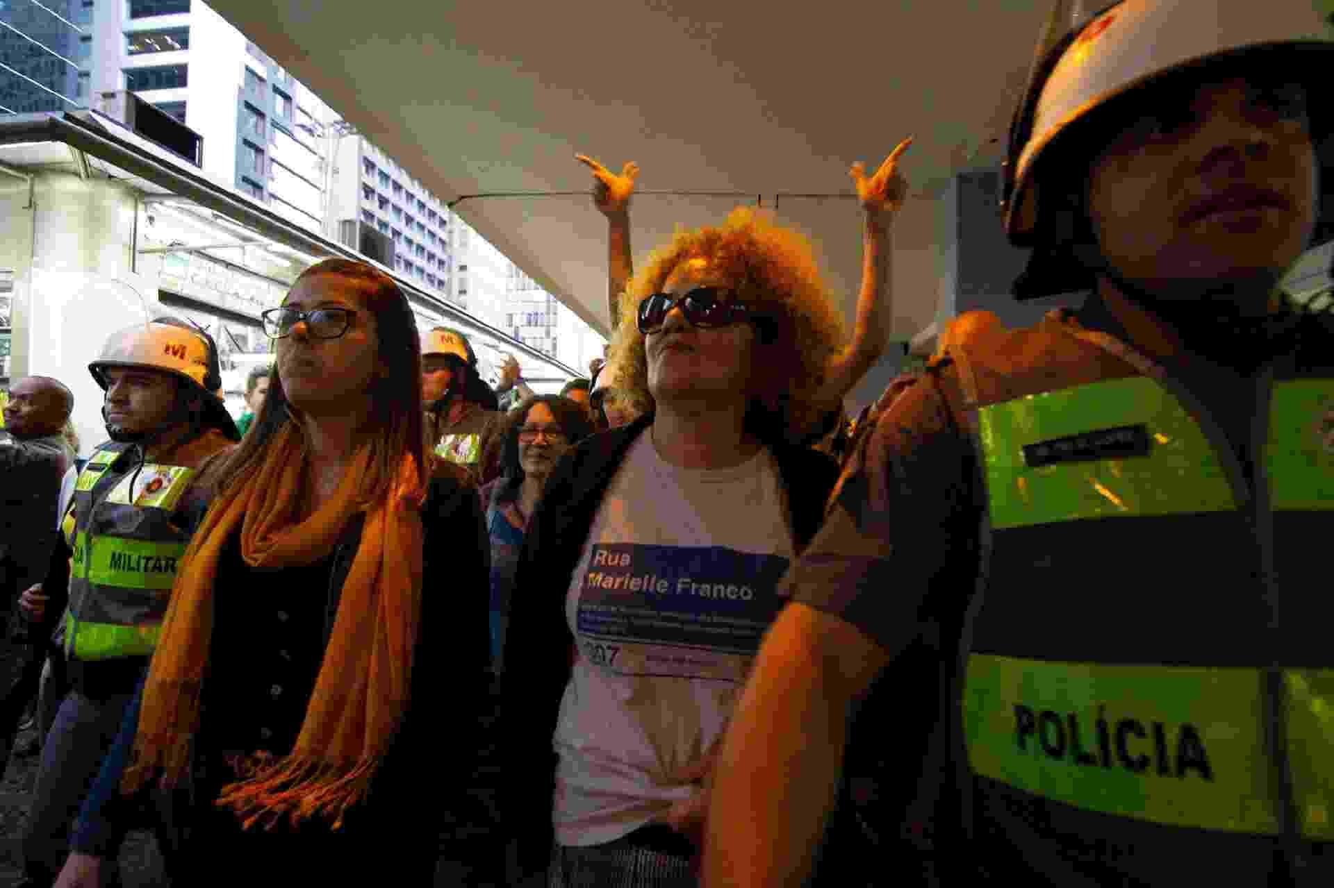 26.mai.2019 - Uma mulher que usava uma camiseta em homenagem à vereadora morta Marielle Franco é escoltada por policiais militares após ser hostilizada ao final da manifestação em favor do presidente Jair Bolsonaro na tarde deste domingo na avenida Paulista - KEVIN DAVID/A7 PRESS/ESTADÃO CONTEÚDO
