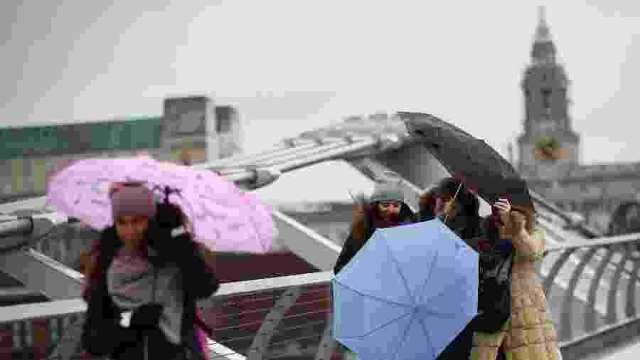 Pessoas lutam para segurar seus guarda-chuvas abertos durante a tempestade Dennis, em Londres  - Hannah McKay/Reuters
