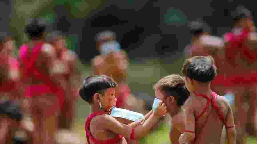 Menino da etnia ianomâmi coloca máscara em outra criança em Alto Alegre, Roraima - ADRIANO MACHADO