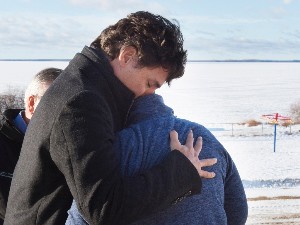 29.jan.2016 - No Canadá, o primeiro-ministro Justin Trudeau abraça e conforta Phyllis Longobardi, funcionária da escola da remota cidade de La Loche, que foi vítima de um atirador em massa. Político visitou o local, conversou com membros da comunidade e deixou flores para homenagear vítimas da tragédia