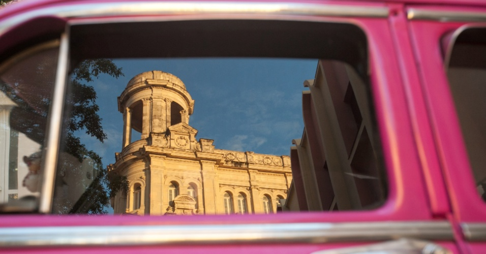 24.mai.2016 - Prédio cubano refletido na janela de um carro antigo americano. A arquitetura de Havana é composta pelos estilos ocidentais mais proeminentes desde o período colonial