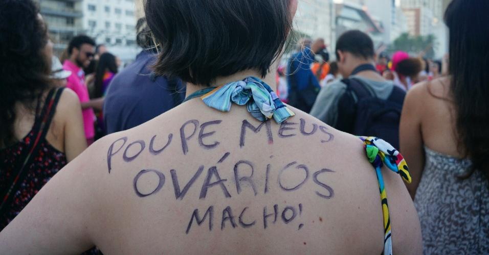 """2.jul.2016 - Mulher com a frase """"Poupe meus ovários, macho!"""" escrita nas costas participa da Marcha das Vadias na praia de Copacabana, no Rio"""