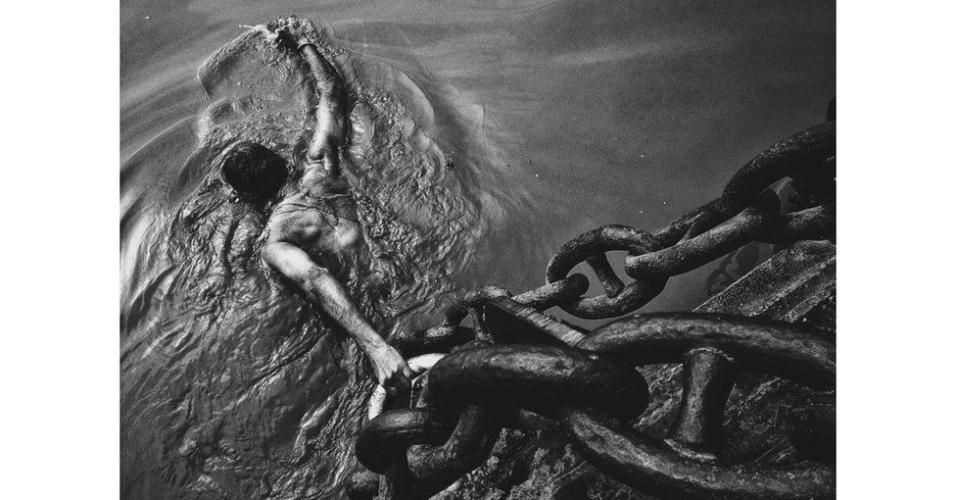"""Essa foto de Xia Zhenkai, de Guandong, na China, ficou em primeiro lugar na categoria """"Gente"""". A imagem retrata um homem se banhando no rio Ganges, na Índia."""