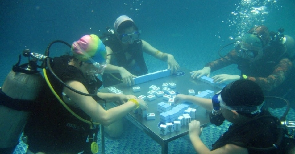 18.jul.2016 - Para sair da rotina e se refrescar durante o verão chinês, mergulhadores brincam de mahjong,  jogo em que é preciso encontrar peças iguais, embaixo d'água em uma piscina em Chongqing