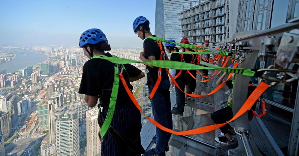 28.jul.2016 - Visitantes usam protetores para apreciar a vista em passarela de vidro ao lado de fora do 88º andar da torre Jinmao, em Xangai, na China. A passarela de 60 metros de comprimento e 1,2 metros de largura foi oficialmente aberta ao público hoje