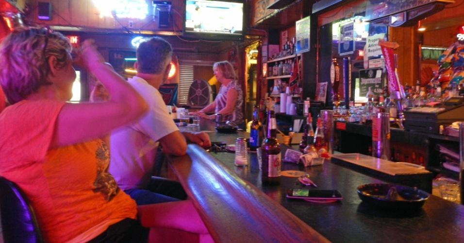 6.out.2016 - Pessoas assistem ao noticiário e bebem em bar de Titusville, na Flórida, na expectativa pela passagem do furacão Matthew
