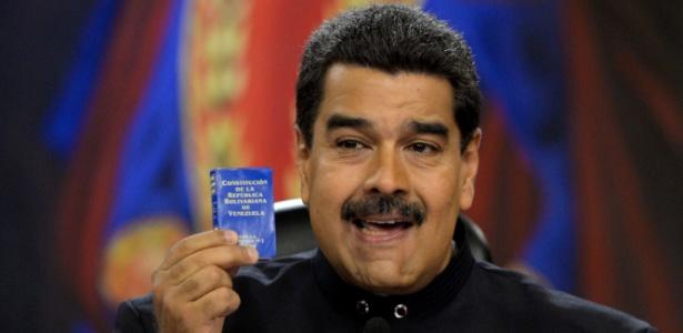 22.jul.2017 - O presidente venezuelano Nicolás Maduro mostra a constituição do país durante entrevista à imprensa estrangeira