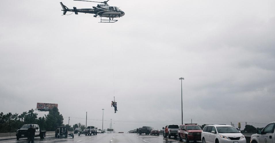 27.ago.2017 - Helicóptero leva pessoa durante resgate na região de Meyerland, em Houston, que foi atingida pelas enchentes provocadas pela tempestade Harvey