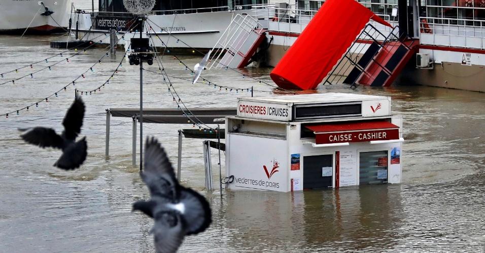 28.jan.2018 - O nível do rio Sena, em Paris, continua a subir após dias de chuvas intensas. Na foto, um posto de venda de ingressos para balsas está parcialmente submerso